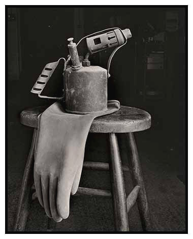 blowlamp on stool with glove